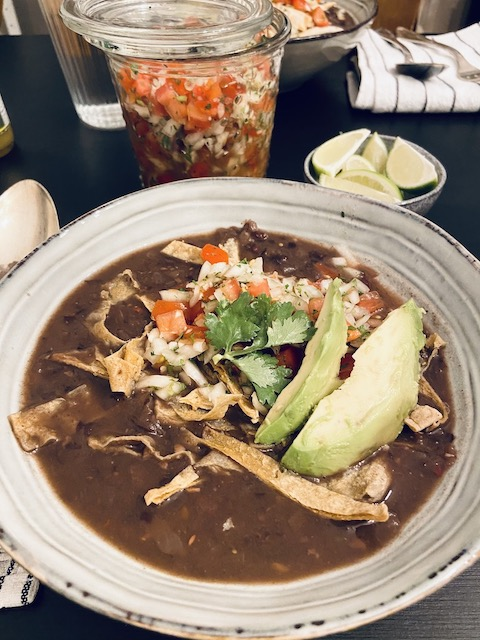 Vegan black bean soup cooked in the instant pot topped with tortilla strips, Pico de Gallo, and avocado